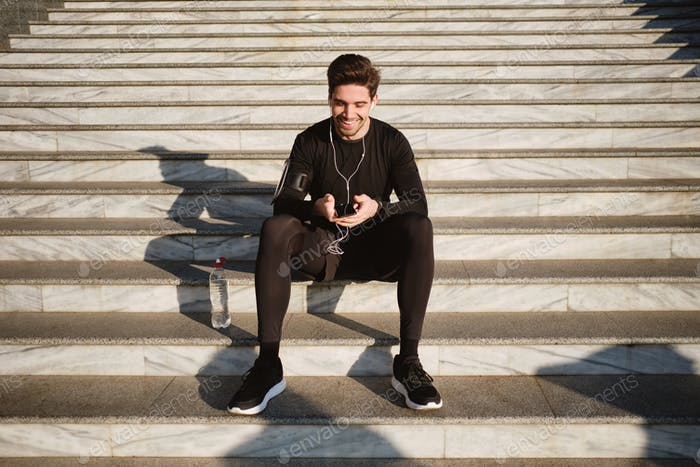 Handsome smiling sporty man sitting on stairs joyfully using cellphone after workout outdoor