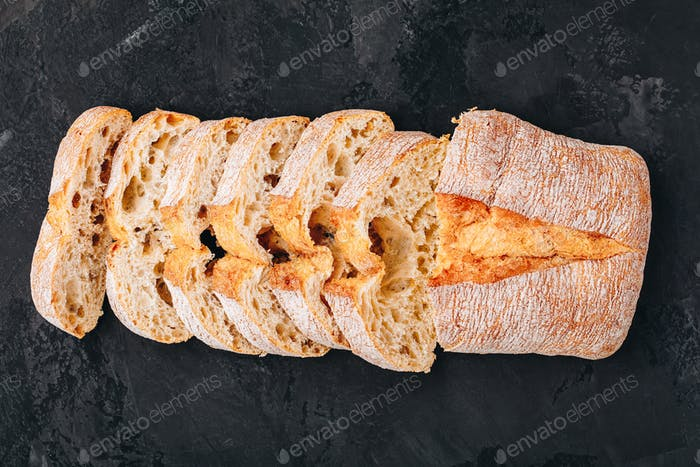 Italian ciabatta bread slices on dark stone concrete background