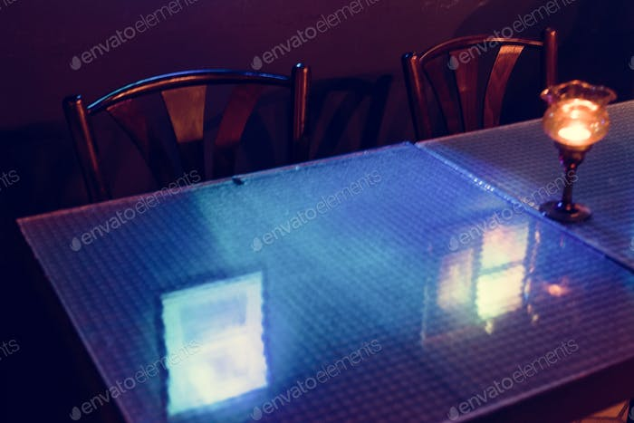 Reflection of blue light on dining table glass in the restaurant