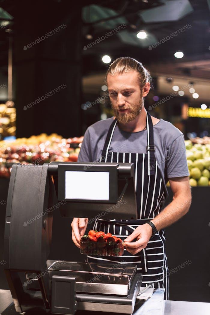 Молодой продавец в фартуке весом клубники на шкале в супермаре
