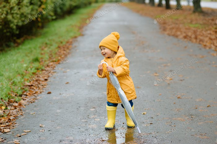 A little girl walks with an umbrella in yellow rubber boots and a waterproof raincoat. Autumn Walk.