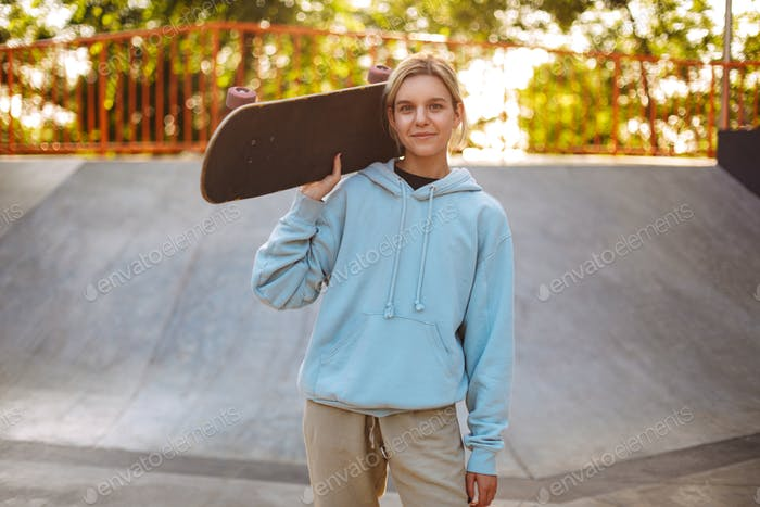 Pretty smiling girl in hoodie holding skateboard on shoulder whi