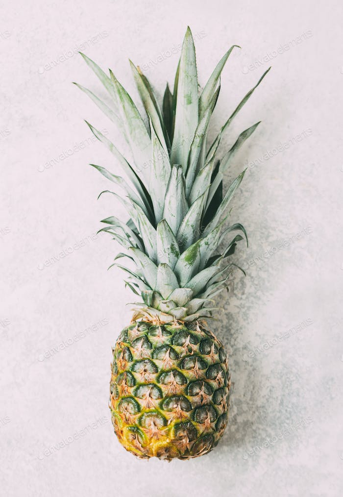 Ripe pineapple on grey textured background
