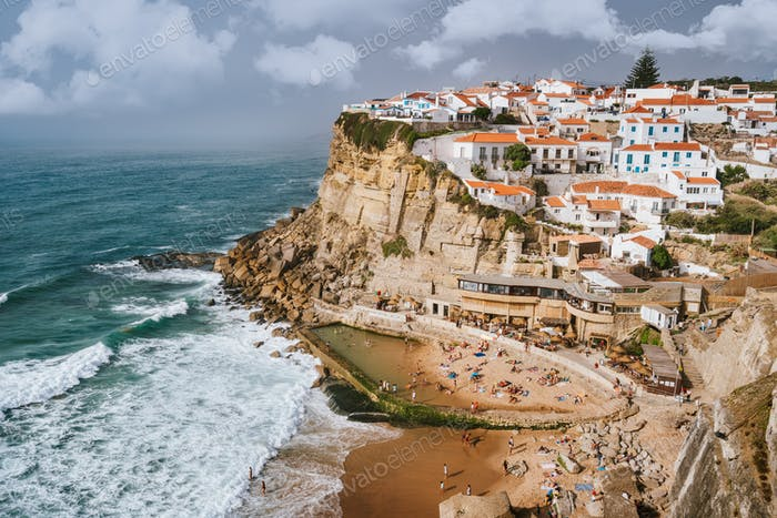 Holiday vibes on beautiful Azenhas do Mar village and wave protected beach. White chalk houses on