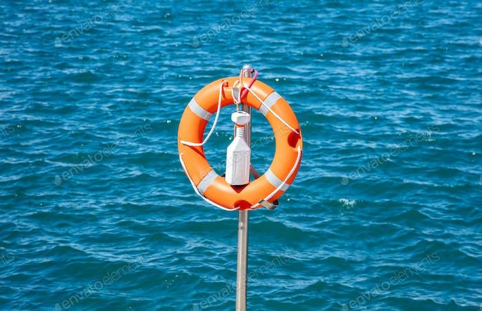 Lifebuoy naranja sobre hierro vertical sobre fondo azul marino.