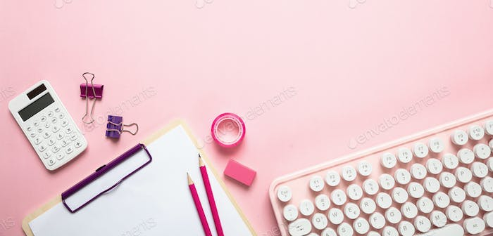 Computer keyboard and office supplies against pink background