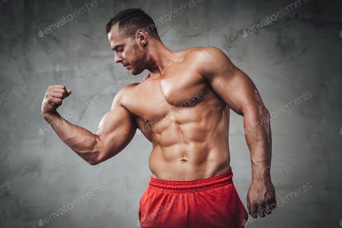 Shirtless muscular sportsman posing in grunge background