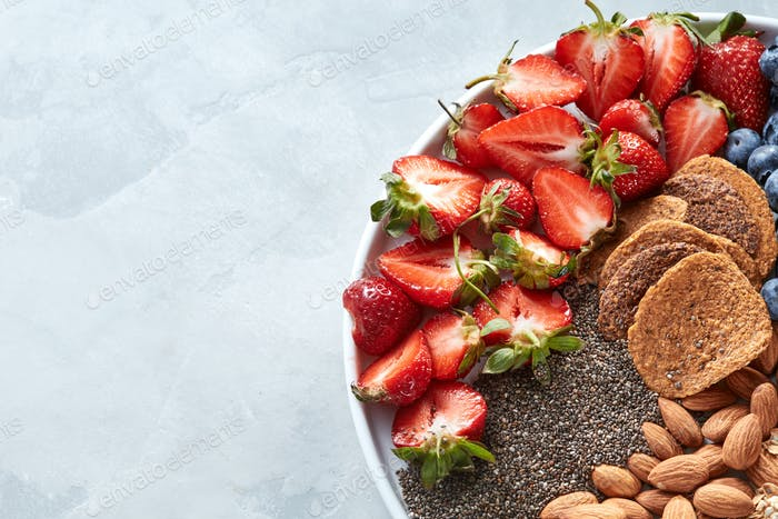 White plate with natural ingredients for cooking dieting vegan food - oatflakes, strawberry, chia
