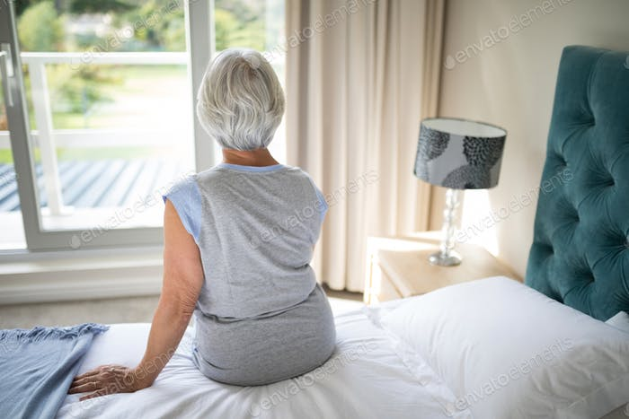 Senior woman sitting on bed in bedroom