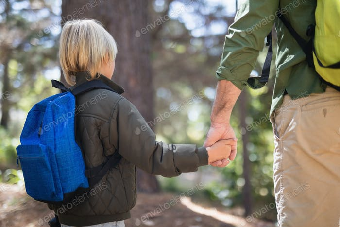 Father and son holding hands while hiking in forest
