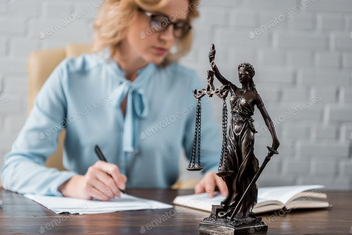 close-up view of lady justice statue and female judge working behind