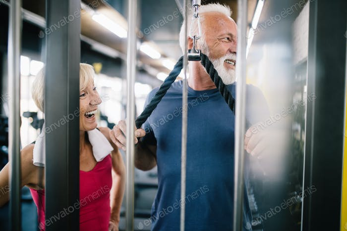 Vital mature couple exercising in the gym