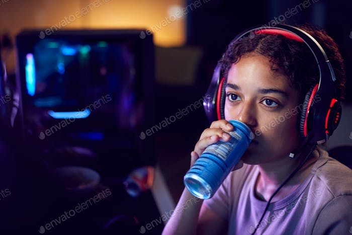 Teenage Girl Drinking Caffeine Energy Drink Gaming At Home Using Dual Computer Screens At Night