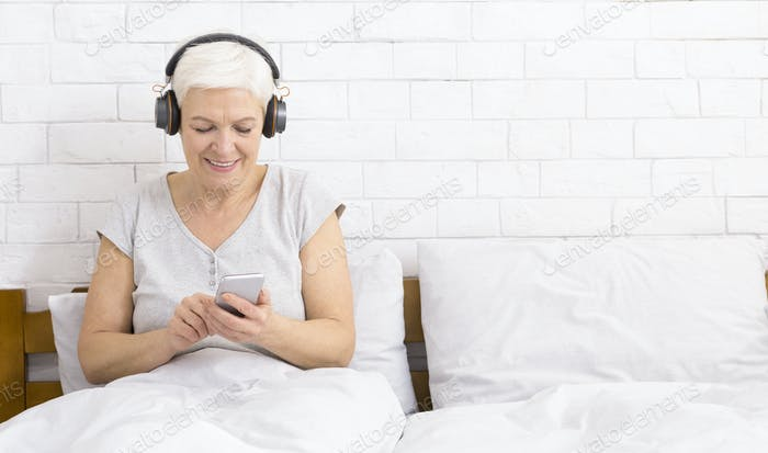 Senior woman listening to music with wireless headphones in bed