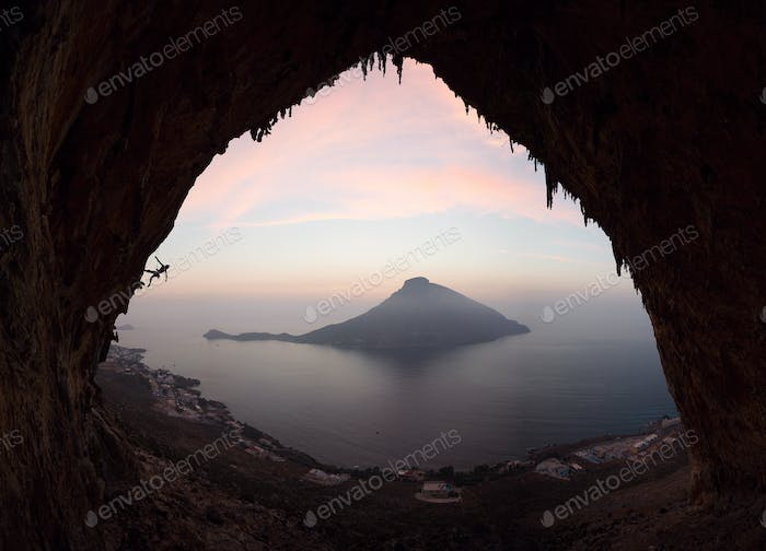 Silhouette of a rock climber on a cliff against picturesque view of Telendos Island at sunset.