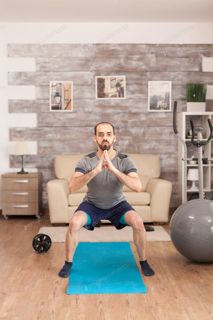 Fit man training his legs on yoga mat