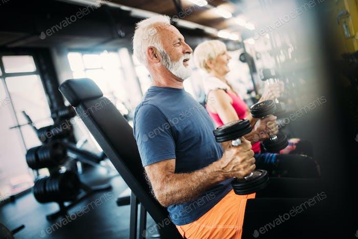 Senior Mann in der Turnhalle tun Übung, um gesund zu bleiben