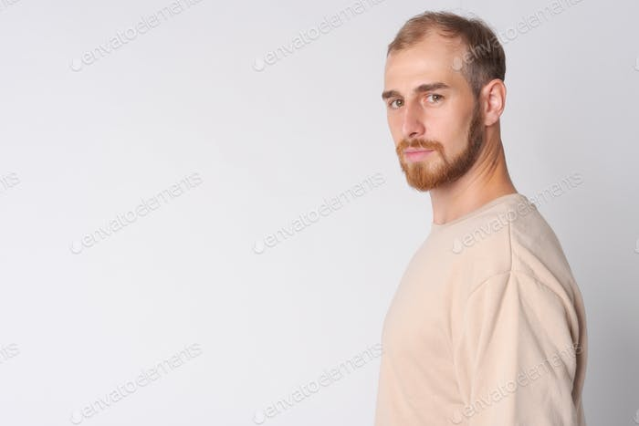 Profile view of young bearded man looking at camera