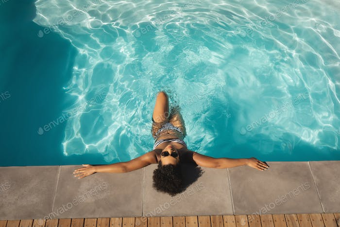 Young woman with sunglasses leaning on edge of pool in backyard of her home