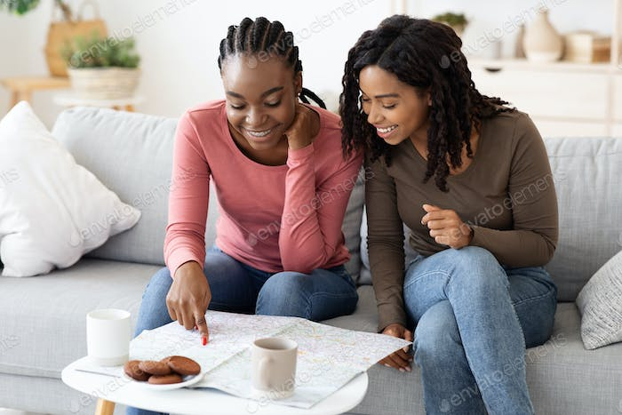Cheerful african american women choosing destination to travel