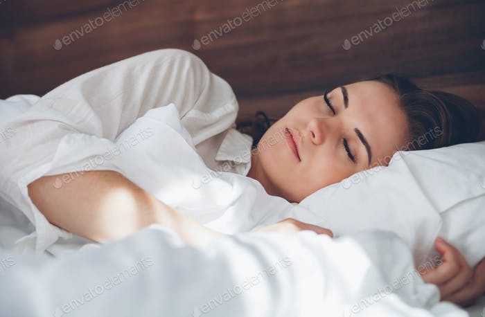 Pretty woman in modern apartment peacefully sleeping at morning