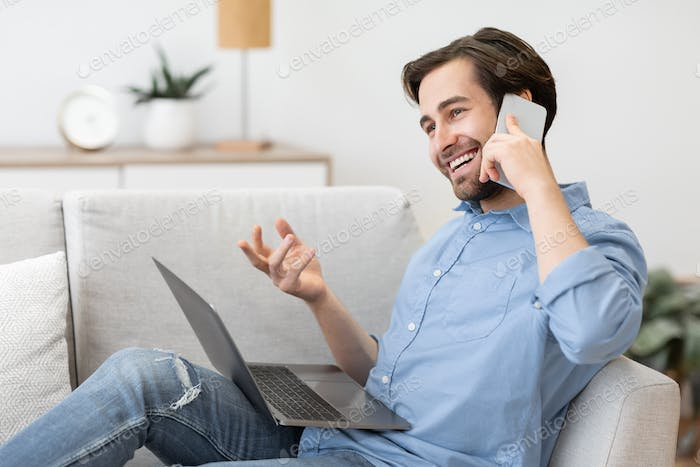 Cheerful Guy Talking On Phone Sitting With Laptop At Home