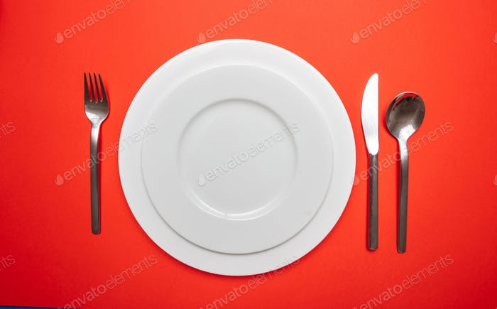 Set of empty white plates and cutlery on red, orange color background
