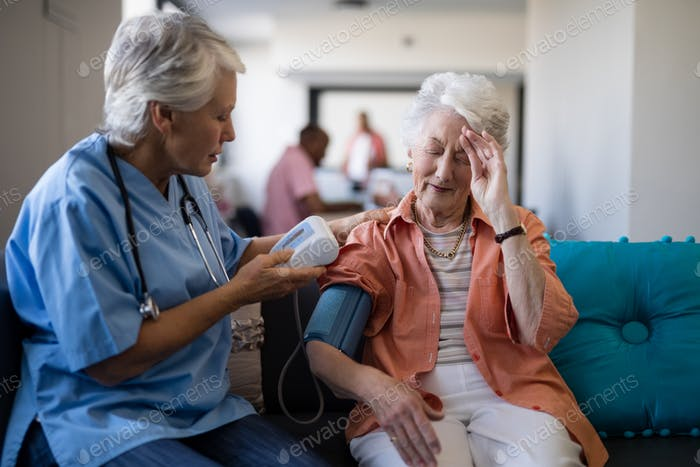 Senior woman complaining about headache to doctor