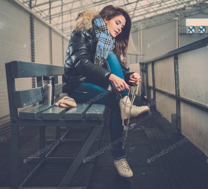Fröhlich Mädchen setzen auf Schlittschuhe auf Eisbahn