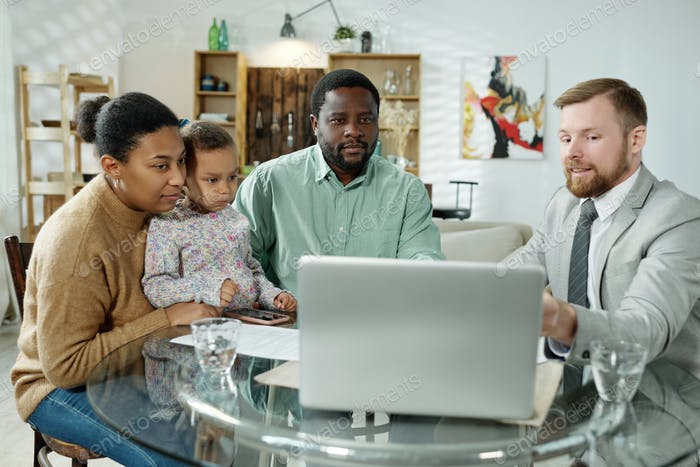Advise and ethnic family watching laptop