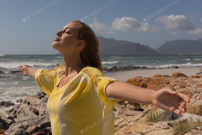 Beautiful woman standing on the rock with arms outstretched on the beach on a sunny day