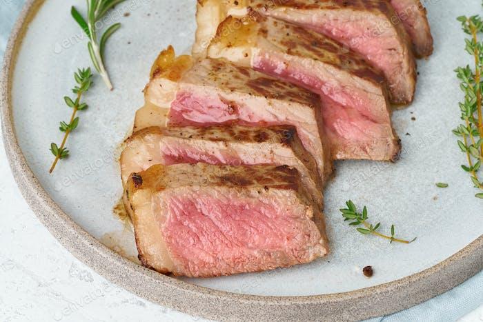 Keto ketogenic diet beef steak, striploin on gray plate on white background. Paleo food