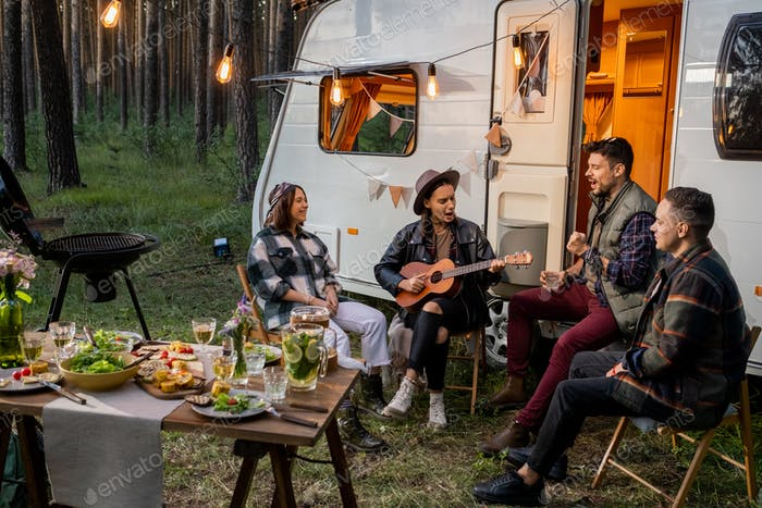 Friendly company sitting by house on wheels and singing songs