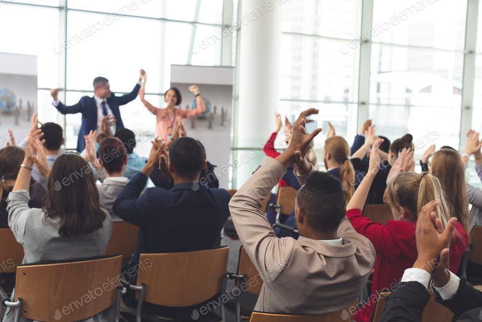 Diverse business people applauding at business seminar in office building