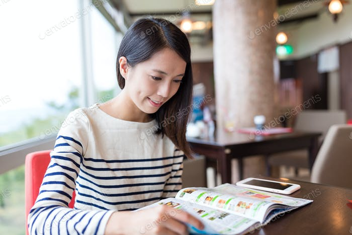 Woman reading magazine in coffee shop