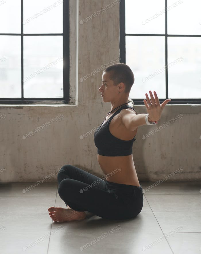 athletic woman doing yoga exercise in loft interior