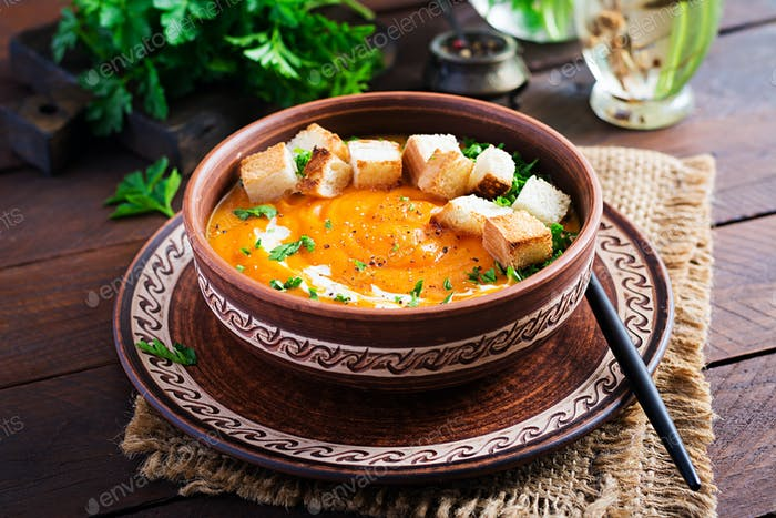 Kürbissuppe in einer Schüssel serviert mit Croutons und Petersilie. Vegane Diät-Suppe. Vegetarisches Essen.