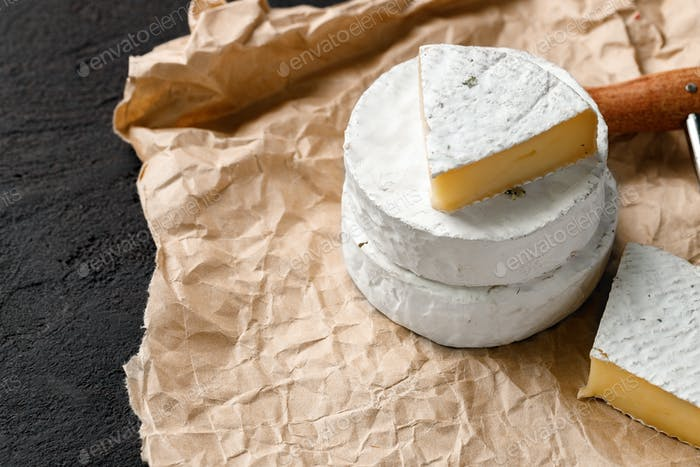 Pieces of camembert cheese on crumpled paper