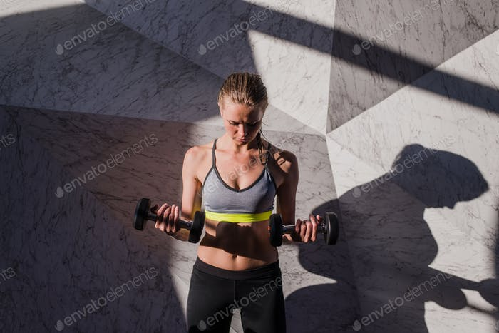 Attractive young athlete with muscular body exercising crossfit. Woman in sportswear doing crossfit
