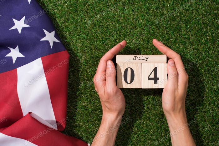 Man Holding Calendar With 4th July Date With American Flag