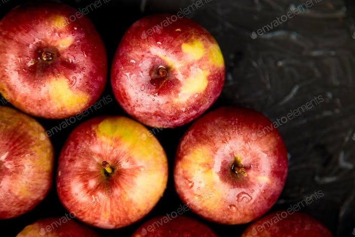 Fresh organic red apples on black background.