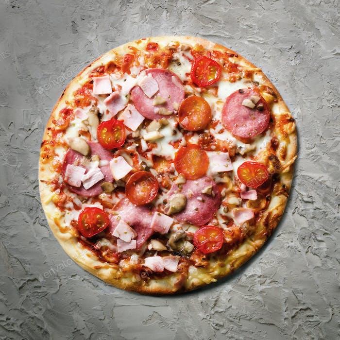 Frische italienische Pizza mit Pilzen, Schinken, Tomaten, Käse auf grauem Betongrund. Kopierbereich