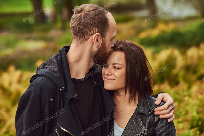 Happy modern couple in a park. Enjoying their love and nature.