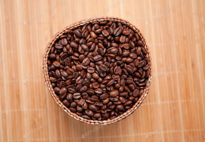 Many roasted coffee seeds in a wooden basket