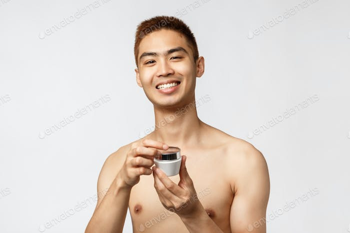 Beauty, people and leisure concept. Handsome asian naked man open skincare cream, smiling pleased