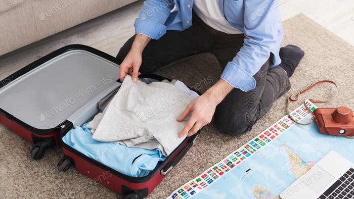 Man packing suitcase at home, sitting on floor