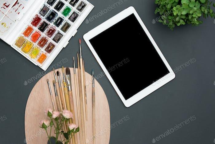 Der Arbeitsbereich des Künstlers mit Laptop, Farben, Pinsel, Blumen auf schwarz