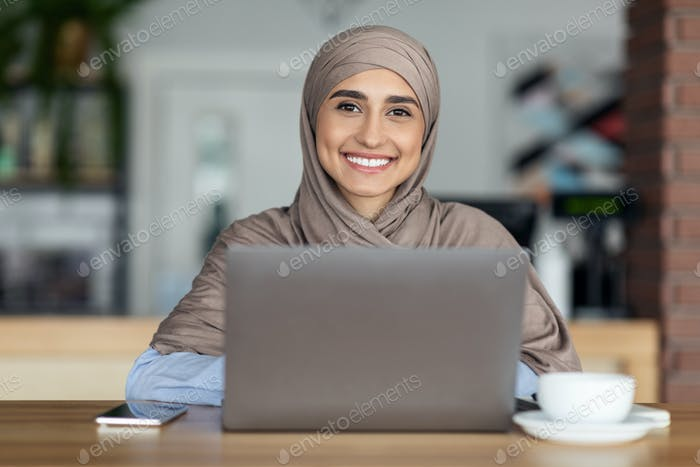 Cheerful muslim woman in hijab working online at cafe