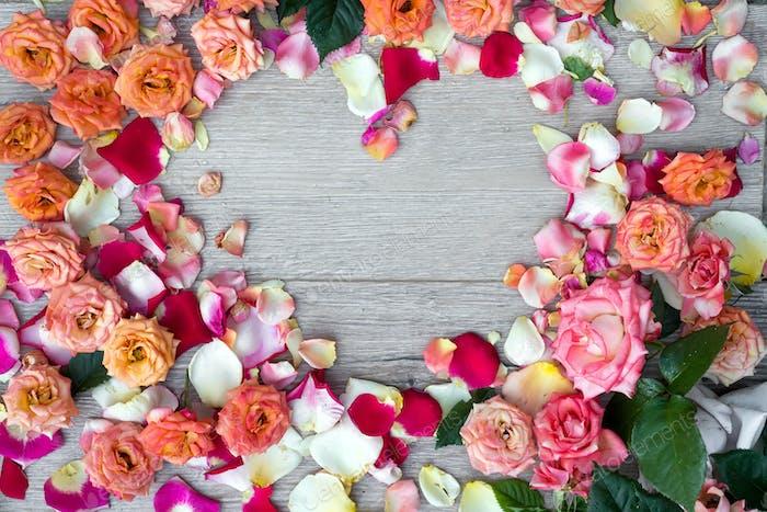 Rahmen Herz aus Rosenblüten auf Holzhintergrund für Valentinstag. Flache Verlegung, Kopierraum