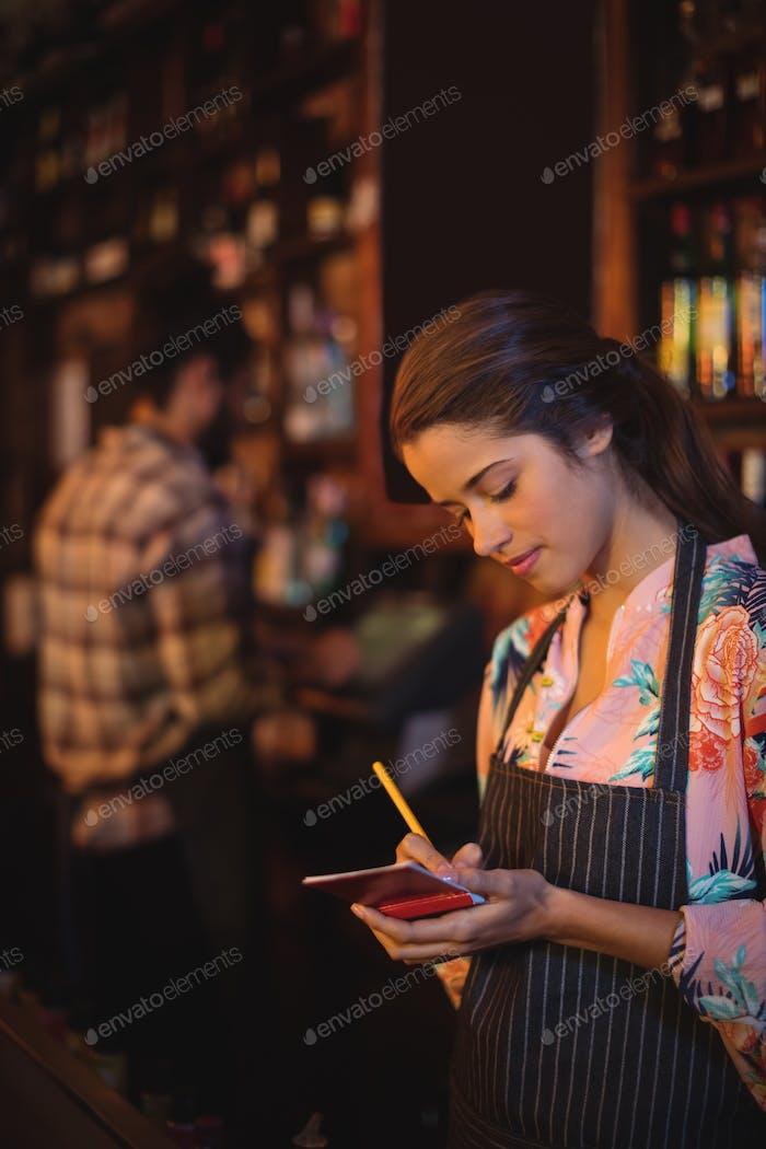Kellnerin nimmt eine Bestellung auf Notizblock am Schalter